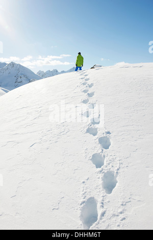 Man standing in snow with footprints, Kuhtai, Austria - Stock Photo