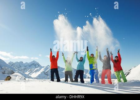 Friends throwing snow mid-air, Kuhtai, Austria - Stock Photo