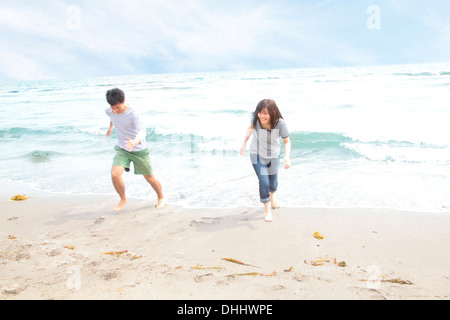 Young couple running away from tide - Stock Photo
