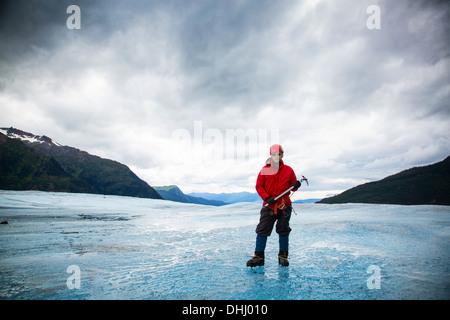 Man with ice pick on Mendenhall Glacier, Alaska, USA - Stock Photo