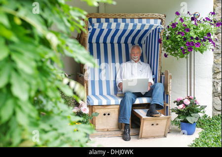 Senior man using laptop on garden seat - Stock Photo