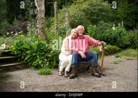 Portrait of senior couple sitting in garden - Stock Photo