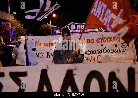 Thessaloniki, Greece. 12th Nov, 2013. A demonstrator holds a flag of an antiracism organization during the march. - Stock Photo