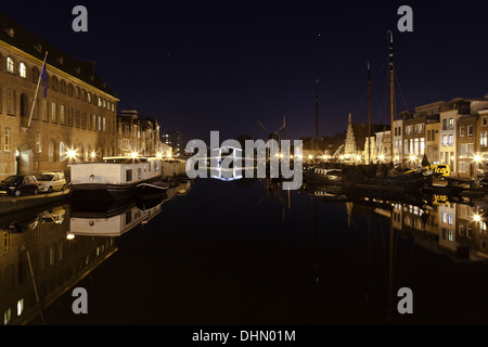 Buildings boats and bridge illuminated at night and reflected in Leiden's Galgewater, - Stock Photo