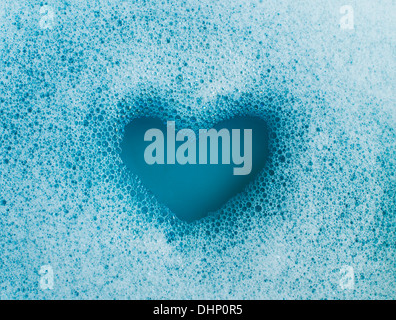 Heart shape created out of soap suds - Stock Photo