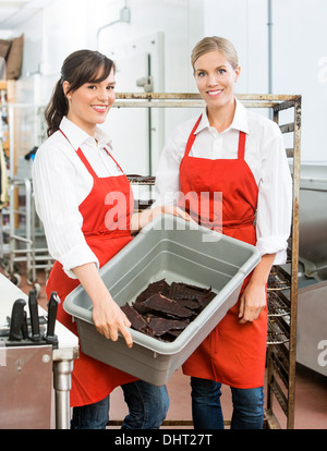 Beautiful Workers Carrying Beef Jerky In Basket At Shop - Stock Photo