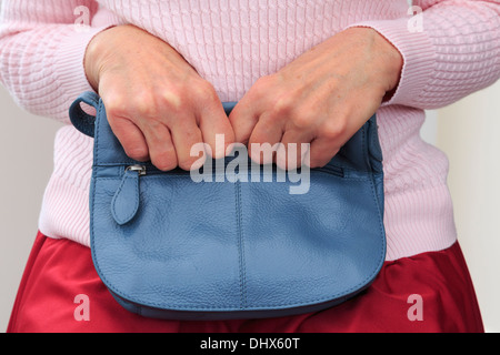 Insecure senior woman sitting and tightly clutching a handbag on her lap with two hands close to her for security. - Stock Photo