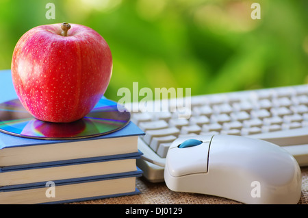 Red apple on book, DVD and mouse - Stock Photo
