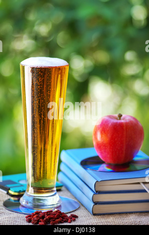 Cold beer and apple on books - Stock Photo