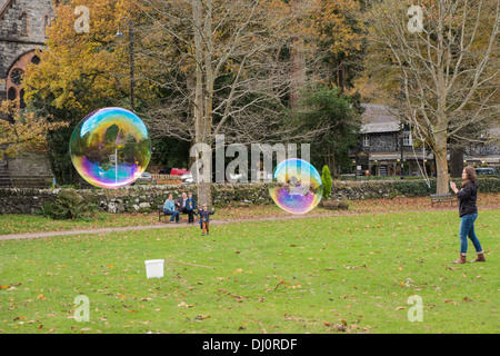 A woman makes two large soap bubbles showing rainbow colours whilst children watch in awe. Betws-y-Coed, Conwy, - Stock Photo