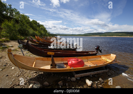 Wooden boats with outboard motors for salmon fishing on river Teno, the natural border between Norway and Finland - Stock Photo