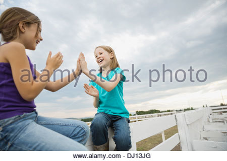 Smiling sisters sitting on fence outdoors - Stock Photo
