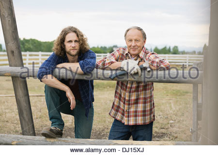 Portrait of father and son leaning on wooden railing - Stock Photo