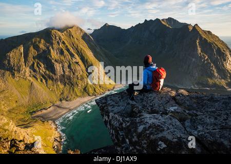 Female hiker enjoying view of Kvalvika beach from near summit of Ryten, Moskenesoy, Lofoten Islands, Norway - Stock Photo