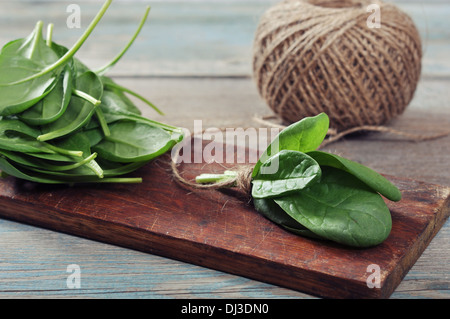 Fresh spinach leaves on wooden cutting board closeup - Stock Photo