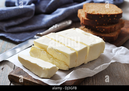 Sliced butter on wooden cutting board closeup - Stock Photo