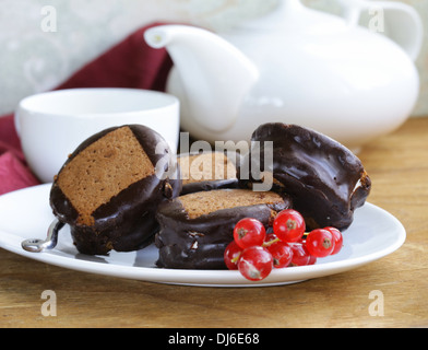 chocolate mini cakes decorated with currants on a white plate - Stock Photo