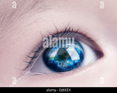 Closeup of a child's blue eye with the Earth globe, world map reflecting in it - Stock Photo