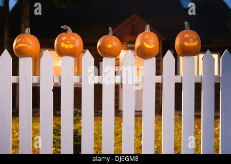 Jack-O-Lantern Faces Stuck On Top Of White Picktet Fence With A House In Background At Twilight During Fall In Alaska. - Stock Photo