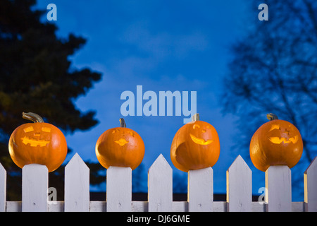 Jack-O-Lantern Faces Stuck On Top Of The Fence Boards Of White Picktet Fence At Twilight During Fall In Anchorage, - Stock Photo
