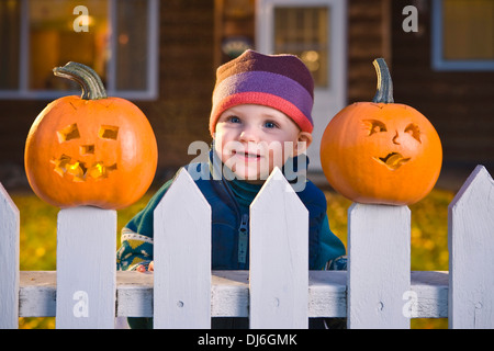 Infant Girl Peeks Between Jack-O-Lantern Faces Stuck On Top Of The Fence Boards, House In Background At Twilight, - Stock Photo