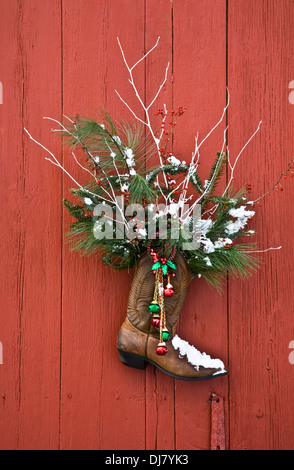 Christmas wreath on door, ranch cowboy boot with bells and evergreen branches on an old red barn door in New Jersey, - Stock Photo