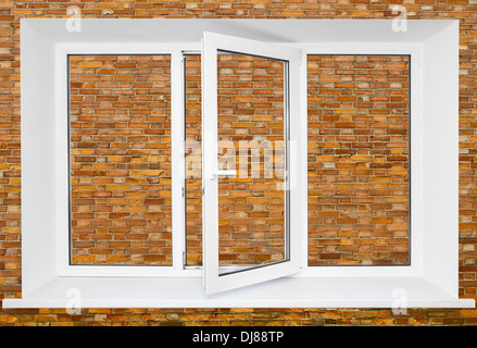 White plastic triple door window on brick wall background - Stock Photo