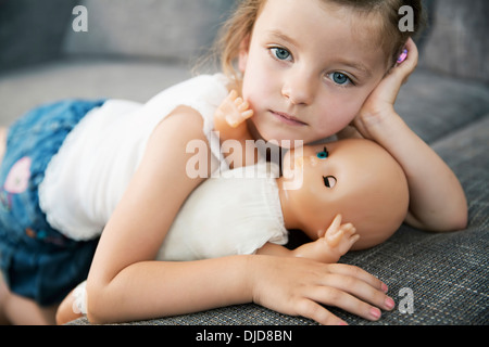 Portrait of little girl lying on sofa with her doll, close-up - Stock Photo
