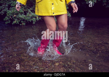 Woman in yellow raincoat and red gumboots jumping in water - Stock Photo