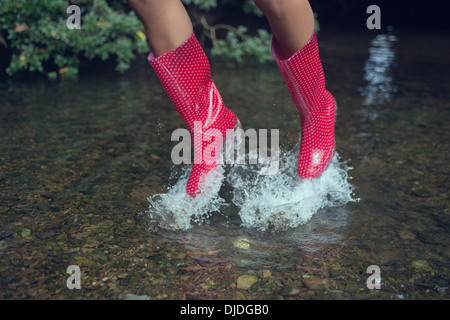 Woman in red gumboots jumping in water - Stock Photo