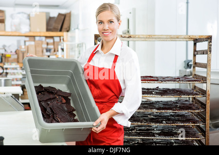 Worker Showing Beef Jerky In Basket At Shop - Stock Photo