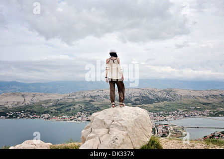 Mid adult woman standing on rock overlooking City Of Pag, Island Pag, Croatia, Europe - Stock Photo