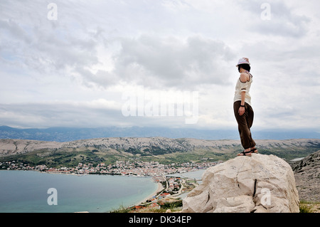 Woman standing on rock overlooking city of Pag, Island Pag, Croatia, Europe - Stock Photo