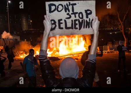 Brazil protest. Revolt, street vandalized by protesters. Banner Don´t stop believing, fire for blocking police. - Stock Photo