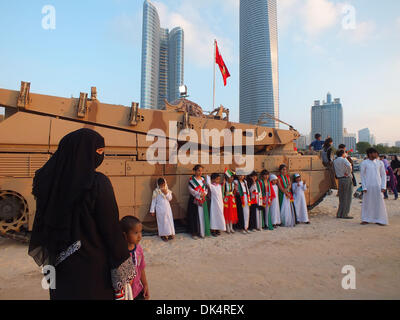 Abu Dhabi. 2nd Dec, 2013. Children pose for photos in front of an armed vehicle subject to the army forces of United - Stock Photo