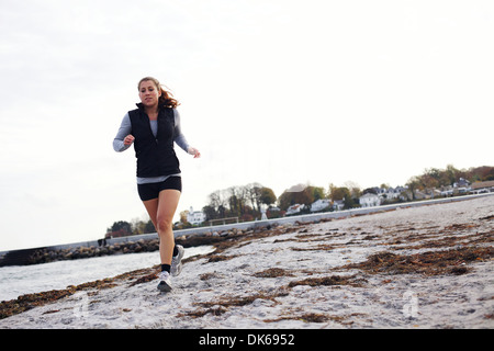 Young woman jogging along beach wearing sports clothing. Healthy female running on sea shore. Female runner exercising - Stock Photo