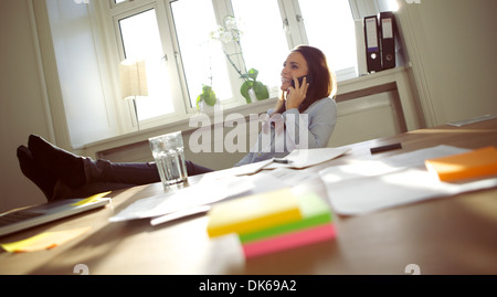 Smiling and beautiful young businesswoman sitting at her desk with legs on table talking on mobile phone smiling. - Stock Photo