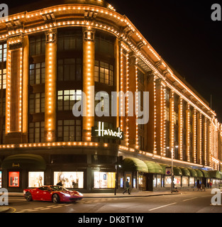 Harrods department store. Facade illuminated at night. Ferrari passes in front of the building - Stock Photo