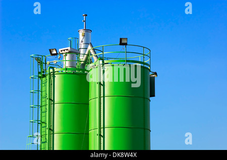 Two green silos against blue sky in a construction site - Stock Photo