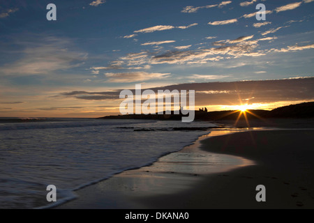 Dunstanburgh Castle, Northumberland, at dawn, viewed from Embleton Bay - Stock Photo