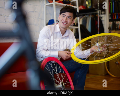 Young man in bike shop holding bicycle wheel - Stock Photo