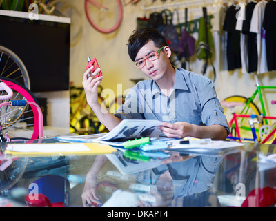 Young man examining bicycle part in bike shop - Stock Photo