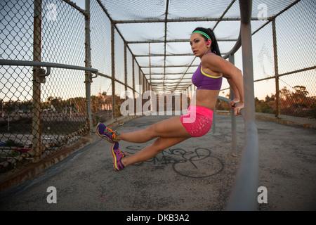 Female jogger stretching on walkway - Stock Photo