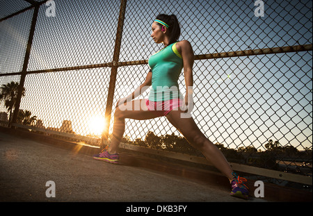 Female runner stretching on walkway - Stock Photo