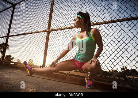 Female runner kneeling and stretching on walkway - Stock Photo