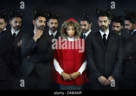 Woman dressed as little red riding hood with businessmen, multiple image - Stock Photo