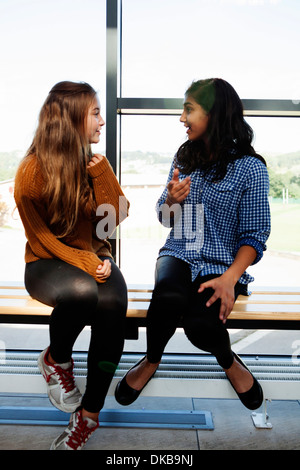 Two teenage schoolgirls sitting chatting in corridor - Stock Photo