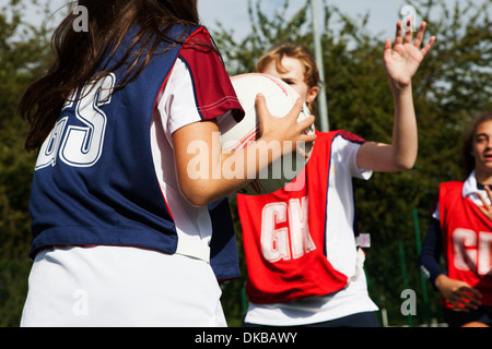 Teenage schoolgirl netball players defending - Stock Photo