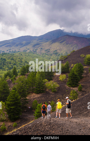 Tourists hiking on an old lava flow from an eruption, Mount Etna, UNESCO World Heritage Site, Sicily, Italy, Europe - Stock Photo