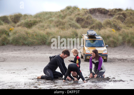 Family with two boys playing on beach - Stock Photo